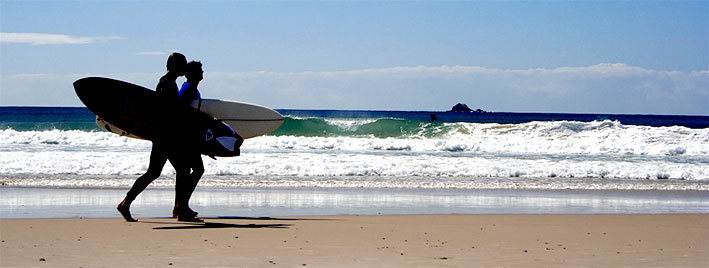 Spaziergang am Strand mit Surfboards in Biarritz